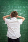 Upset child looking at blackboard full of formulas Stock Images