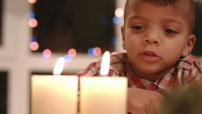 Upset child looking at candle. stock footage