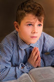 Upset child in shirt praying. Royalty Free Stock Photo