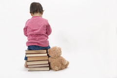 Upset child sitting on books with her teddybear stock images