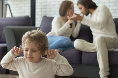 Upset child son puts fingers in ears while parents fighting. Child son puts fingers in ears while parents fighting at home, stressed boy suffering from mom and Stock Photography