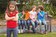 Upset child standing away from group. Sitting on a bench Royalty Free Stock Image