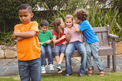 Upset child standing away from group Stock Image