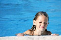 Upset child in swimming pool. A caucasian child crying and upset in a swimming pool holding on to the edge Royalty Free Stock Image