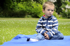 Upset child waiting in park Stock Photo