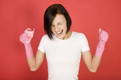 Upset cleaning up woman. Young screaming woman in pink rubber gloves holding in hand washcloth. She's looks like very angry. Front view royalty free stock photography