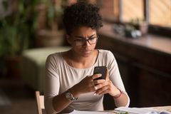Upset confused african woman holding cellphone having problem with phone stock photography