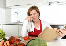 Upset cook woman bored and frustrated reading recipes book in home kitchen in stress. Young beautiful cook woman bored and confused wearing red apron sitting at Stock Photo