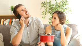 Upset couple calling insurance watching home leaks stock footage