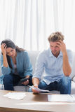 Upset couple doing their accounts. In the living room stock images
