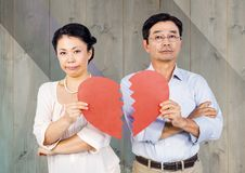 Upset couple holding broken heart. Against wooden background Stock Photo
