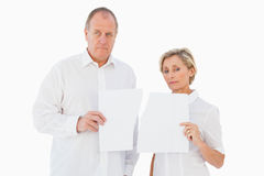 Upset couple holding torn piece of paper Royalty Free Stock Images