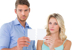 Upset couple holding torn piece of paper Stock Photos