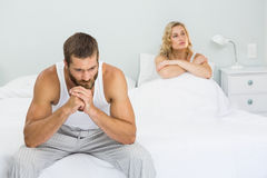 Upset couple ignoring each other after fight on bed. In bedroom Royalty Free Stock Images