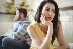 Upset couple ignoring each other on sofa. In living room Stock Image