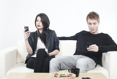 Upset couple looking to mobile phones Royalty Free Stock Photos