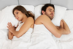 Upset couple lying back to back in bed Royalty Free Stock Image