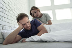 Upset couple lying in bed Stock Photos