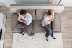 Upset Couple Sitting On Couch royalty free stock image