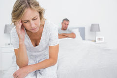 Upset couple sitting on opposite ends of bed after a fight. In bedroom at home stock photo