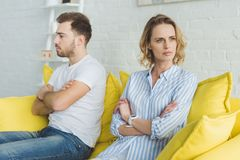 Upset couple sitting on yellow couch after stock image