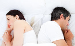 Upset couple sleeping in their bed separately Stock Photos