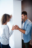 Upset couple standing on opposite sides of the wall Stock Image