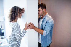 Upset couple standing on opposite sides of the wall Stock Photos