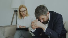 Upset crying businessman patient holding his head by hands talking to his psychoanalyst in her office. Indoors stock footage