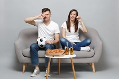 Upset crying couple woman man football fans cheer up support favorite team with soccer ball wiping tears isolated on. Upset crying couple women men football fans stock image