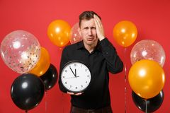 Upset crying young man in classic shirt putting hand on head, holding round clock on red background air balloons. Time. Is running out. Women`s Day Happy New stock photos