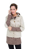 Upset cute brunette in winter fashion phoning Stock Images