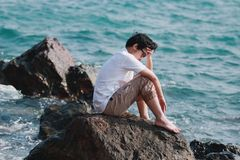 Upset depressed Asian man with hands on face feeling bad at rock of natural seashore.  Royalty Free Stock Image