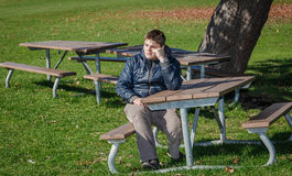 Upset depressed teenage boy sitting alone in autumn park Stock Photography