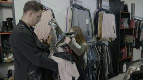Upset disappointed fiancee puts the clothes back to their place in a boutique after fiance refuses to pay for them -. Upset disappointed fiancee puts the clothes stock video footage