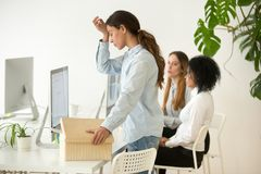 Upset fired dismissed young woman employee packing box leaving w royalty free stock photography