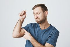 Upset dissatisfied bearded guy wearing blue t-shirt posing at studio tensing muscles to show his biceps, curving lips. Upset dissatisfied bearded guy wearing Stock Image