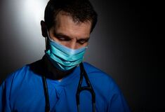 Upset / distraught doctor wearing surgical mask and stethoscope.