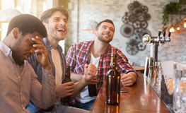 Upset diverse friends watching football in bar royalty free stock images