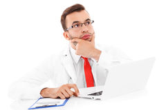 Upset doctor with laptop and documents Stock Photo