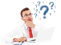 Upset doctor with laptop and documents stock photography