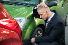 Upset driver looking at car after traffic collision. Upset Driver In Front Of Automobile Crash Car Collision stock images