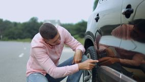 Upset driver looking at scratches and dents on car. Annoyed handsome male driver with handsfree checking his car for scratches and dents outdoors. Frustrated man stock footage