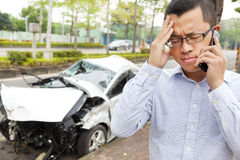 Upset driver talking on mobile phone with crash car. Phone call to help Stock Images