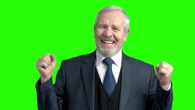 Upset elderly businessman, green background. Senior man in suit gesturing with hands in desperation on chroma key background, slow motion. Grief and problems stock video footage