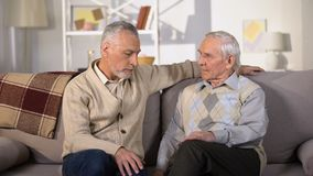Upset elderly male friends talking and hugging at home, support, life problems stock video footage