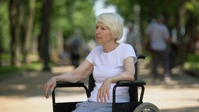 Upset elderly woman sitting in wheelchair at nursing home park, terminal illness stock video
