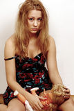 Upset emotional girl. Pretty young woman with upset and emotional expression holding doll Stock Photo