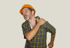 Upset and exhausted construction worker or repair man wearing builder helmet complaining suffering pain in his shoulder after stock photo