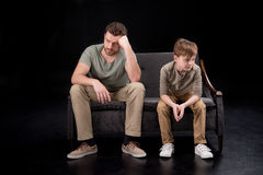 Upset father and son sitting on sofa and looking away. Family problems concept Royalty Free Stock Photo
